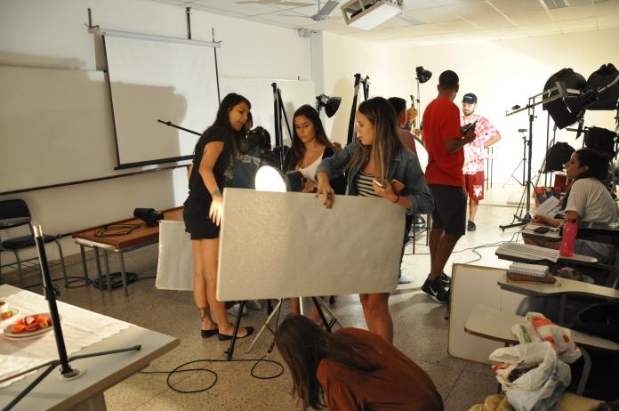 Alunos de publicidade fotografando produtos no estúdio