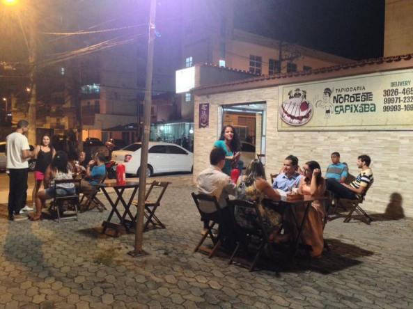 Imagem de um dia de atendimento da tapiocaria com muitas pessoas sentadas e uma atendente.