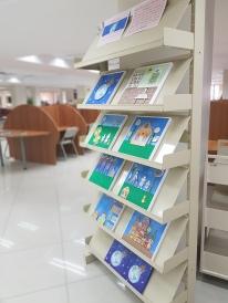 Estante com quadros de azulejo feitos por artista plástica. Ambiente de biblioteca universitária.