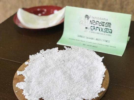Imagem de uma tapioca com um prato e um anúncio da tapiocaria.