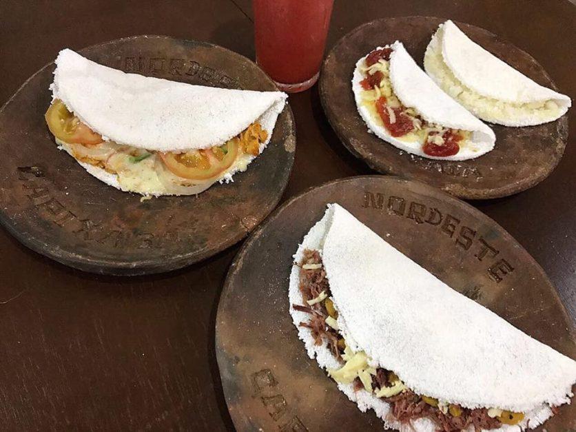 Quatro tapiocas nos pratos da Tapiocaria Nordeste Capixaba disponíveis para escolha no cardápio da empresa.