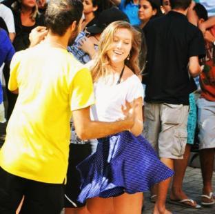 casal dançando forró. mulher veste saia azul e branca e camisa branca. homem veste camisa amarela e está de costas.