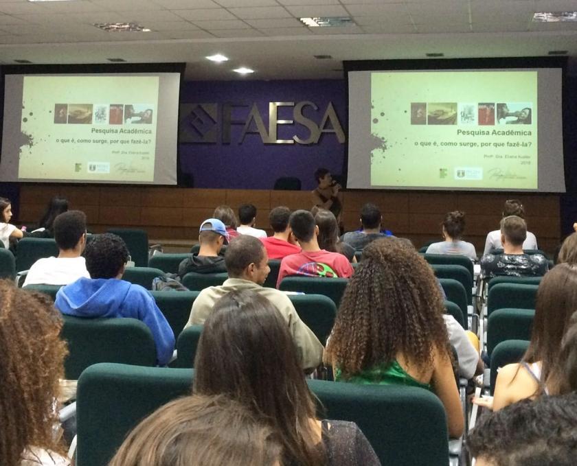 Na foto, alunos assistem palestra da professora Eliane Kuster. A palestrante mostra aos alunos slides de sua pesquisa acadêmica no datashow.