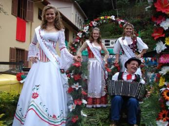 Pessoas vestidas à caráter para festa italiana. Moças usando vestidos longos e senhor sentado tocando acordeon