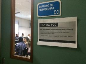 fotografia mostrando os dois ex-alunos que apresentaram o TCC e a professora Zanete Dadalto através do vidro da porta, e na porta está escrito o nome deles e o título dos seus respectivos TCCs