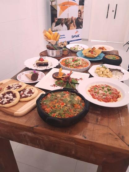 mesa composta por diversos pratos com comidas diferentes, incluindo moqueca, massas, esfirras e sobremesas