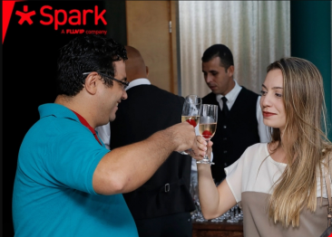 Homem e mulher brindando com taças de espumantes e cerejas dentro