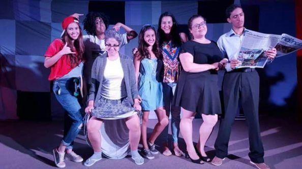 Fotografia exibe um grupo de alunos do curso de Teatro preparados com as roupas de acordo com cada personagem para apresentação do espetáculo.