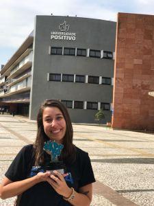imagem retratando a aluna Cristiane Rubim com o prêmio da Exporcom