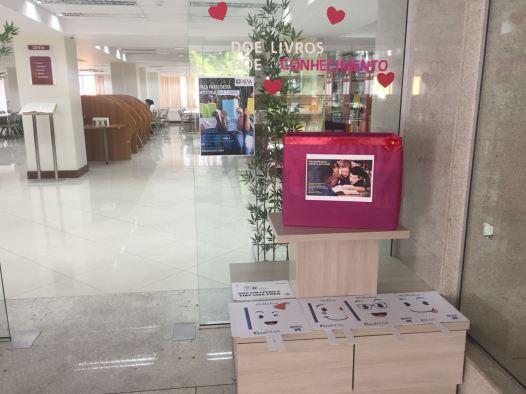 Foto da frente da Biblioteca da Faesa com a caixa para a doação de livros