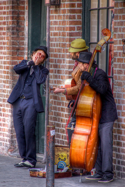 homens tocam gaita, violão e violoncelo na rua