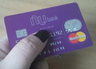 mão com unhas pintadas de preto segurando cartão de crédito
