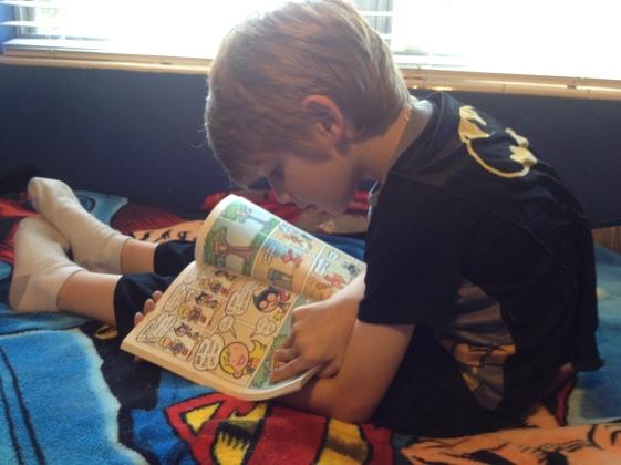 Menino vestindo uma camiseta do batman enquanto lê histórias em quadrinhos