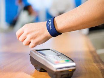 braço com pulseira inteligente e máquina de cartão de crédito