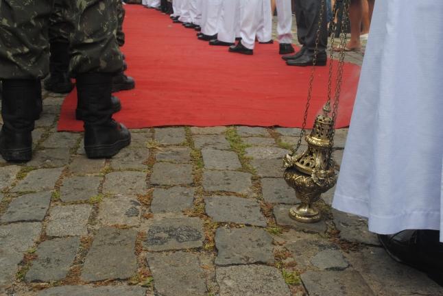 Contraste entre equipamento de membro do clero (incenseira e manto) e de militar (coturno e farda).