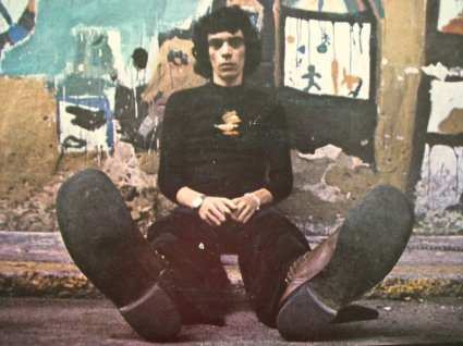 poeta e cantor Sérgio Sampaio sentado encostado a um muro pixado