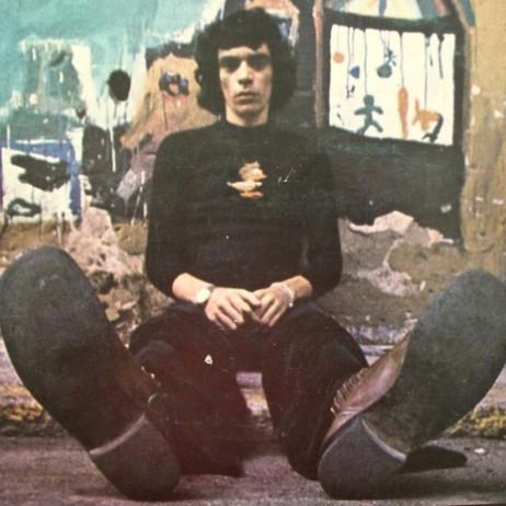 Na foto, o cantor e compositor Sérgio Sampaio sentando em uma calçada.