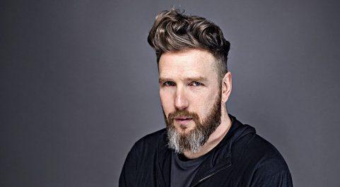 Homem branco, com barba, posando para foto em um estúdio fotográfico.