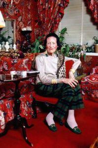 idosa estilosa sentada em poltrona. ambiente vermelho