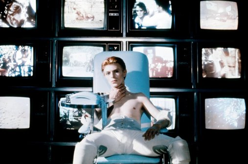 man-who-fell-to-earth-the-1976-006-bowie-seated-in-front-of-bank-of-televisions-00m-ezc.jpg