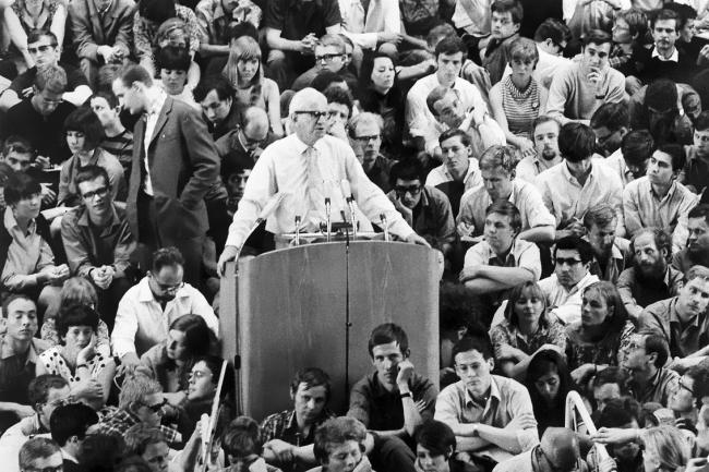 homem faz discurso em púlpito para multidão, imagem em preto e branco
