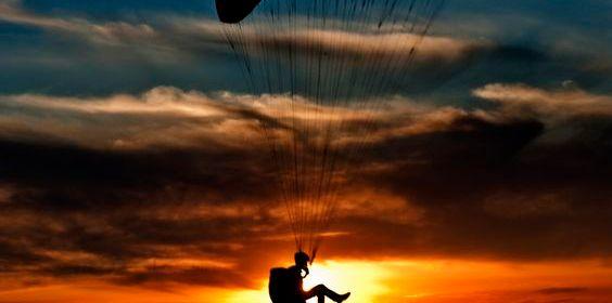 homem em parapente e paisagem solar