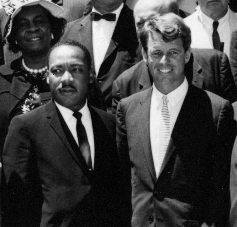 um homem negro e um branco de braço dado