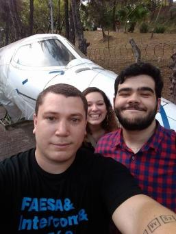 três alunos tiram selfie próximo a um avião em Belo Horizonte