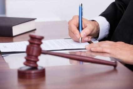audiência com juiz assinando documento