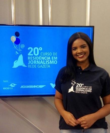 A imagem exibe a ex-universitária selecionada para o projeto Curso de Residência em Jornalismo da Rede Gazeta, Ana Nascimento, diante de uma televisão em um estúdio de TV da empresa.