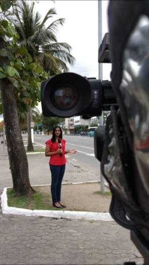 Fotografia exibe ex-universitária Ana Nascimento em via pública em gravação de matéria. A imagem contém uma câmera de televisão ao canto, com a lente aparecendo antes da personagem.