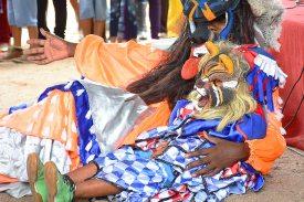 Pessoa com uma criança, ambos fantasiados de foliãs no Encontro Nacional de Folia de Reis