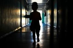 A imagem escura mostra uma garota, que aparenta ser criança, em um sistema prisional brasileiro