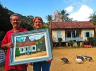 A imagem mostra um casal em primeiro plano com um quadro nas mãos, obra pintada sobre uma paisagem, com alguns animais ciscando no chão.