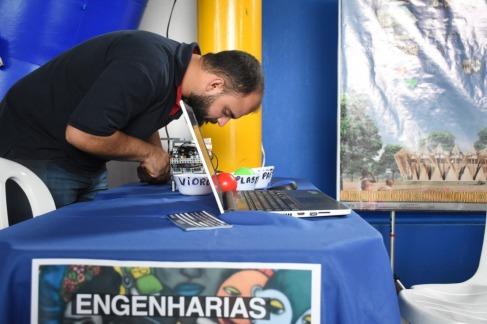 Estudante de engenharia inlcinado para baixo em mesas com panos de cor azul em cima da mesa tem um notebook e vasilhinhas de plastico brancas ao fundo uma parede azul e uma coluna amarela