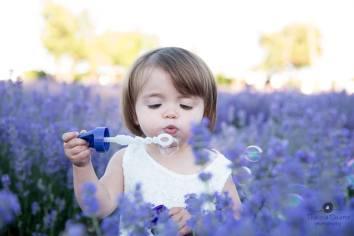 Criança, com roupa branca, em um campo de lavanda (flores roxas) com um objeto nas mãos e bolhas de sabão ao redor dela