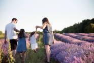 Família em um campo de flores rosas com um homem à esquerda, duas crianças ao meio e uma mulher à direita. Uma das crianças está pulando.