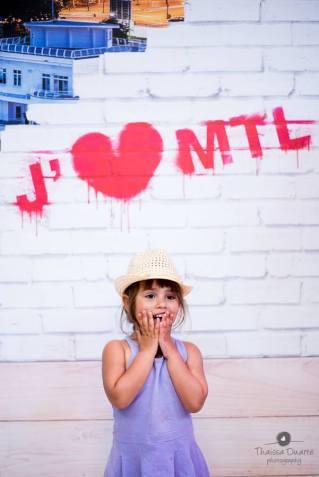 Fotografia de uma menina à frente de um muro com cores e dizeres, com a roupa roxa, um chapéu bege na cabeça e as duas mãos no rosto