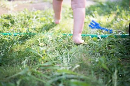 A imagem mostra uma criança andando na grama com alguns detalhes que remetem a um jardim de casa
