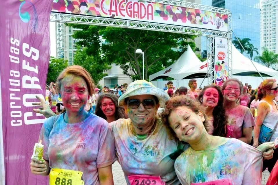 Na linha de chegada da corrida das cores a professora Zanete está toda suja de tinta de várias cores no centro da fillha Dora que tem as cores rosa,amarelo e verde no rosto e Pedro que é o menos sujo. Ao fundo três meninas entram de espiãs na foto e sorriem todas de rosa.