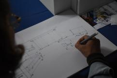 folha xamex na horizontal com um esboço de um quarto desenhado por uma canetinha cinza, com uma cama beliche a esquerda do desenho, uma janela central e uma mesa com um computador e uma cadeira a direita