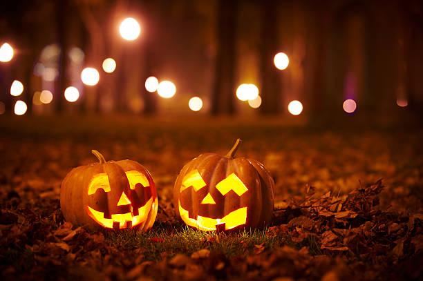 No chão de grama, a noite, duas abóboras cortadas com carinhas iluminadas. No fundo luzes de lanternas