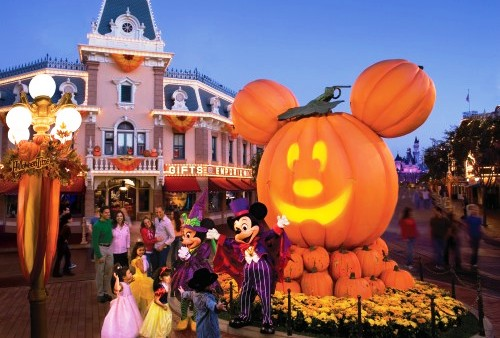 Mickey e Minnie na frente de uma abóbora gigante no formato do Mickey, crianças vestidas de princesas. No fundo uma loja com decoração laranja, o céu azul e na frente um poste azul