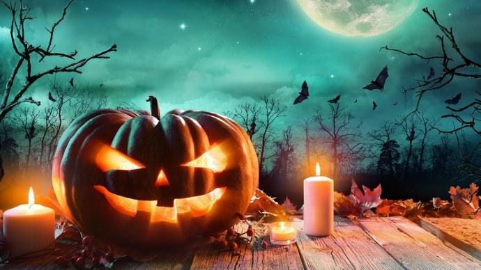 Abóbora iluminada por velas e algumas delas ao lado, uma noite sobria com a lua cheia
