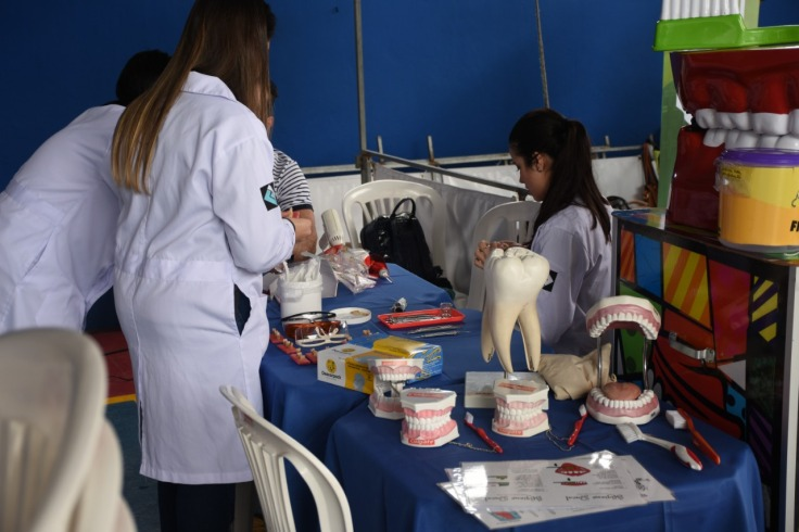 mesa azul com acessórios de educação de higiene bucal, como bocas e dentes grandes para ensino. alunos de odontologia de jaleco, dois a esquerda em pé e uma a direita sentada em uma cadeira de plastico branca.
