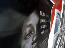 Cartaz sobre refugiados exibido na passarela que liga o bloco 6 ao restante.