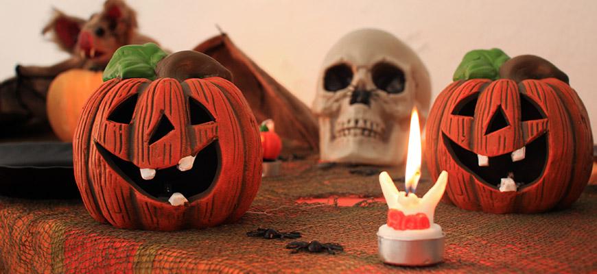 Em uma mesa,uma toalha laranja, uma abóbora cortada com carinha, uma caveira e uma vela