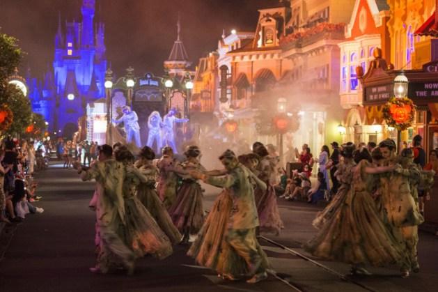 Vários zombies em uma das ruas da Disney, o castelo ao fundo iluminado de azul e lojas iluminadas de vermelho ao lado