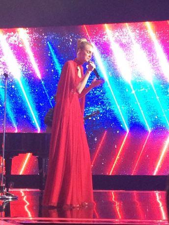 Carol Trentini cantando, no fundo um telão vermelho, azul e rosa com listras brancas