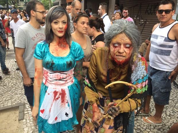 Duas mulheres vestidas de Zombies, o chão de pedras e pessoas atrás olhando para elas